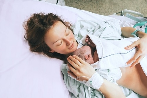 new mom with newborn during postpartum recovery